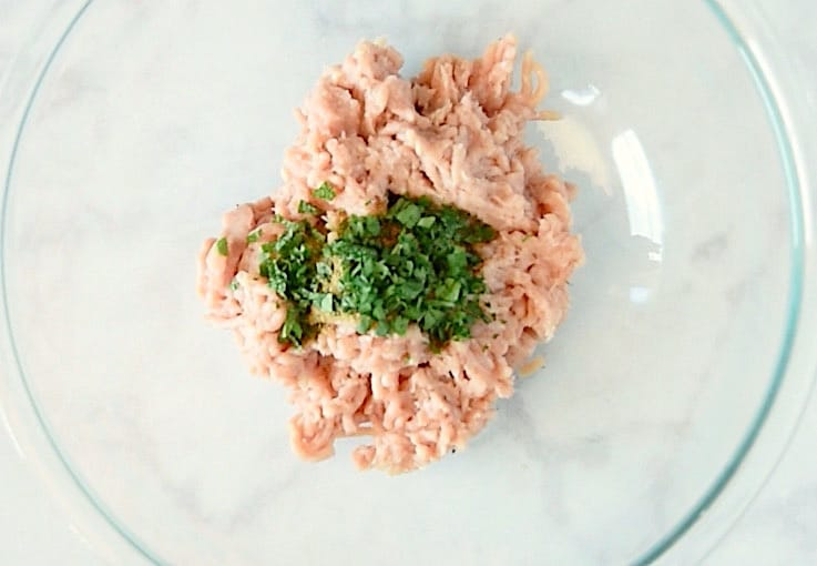 Ground chicken in a glass bowl with fresh mint, cilantro and spices