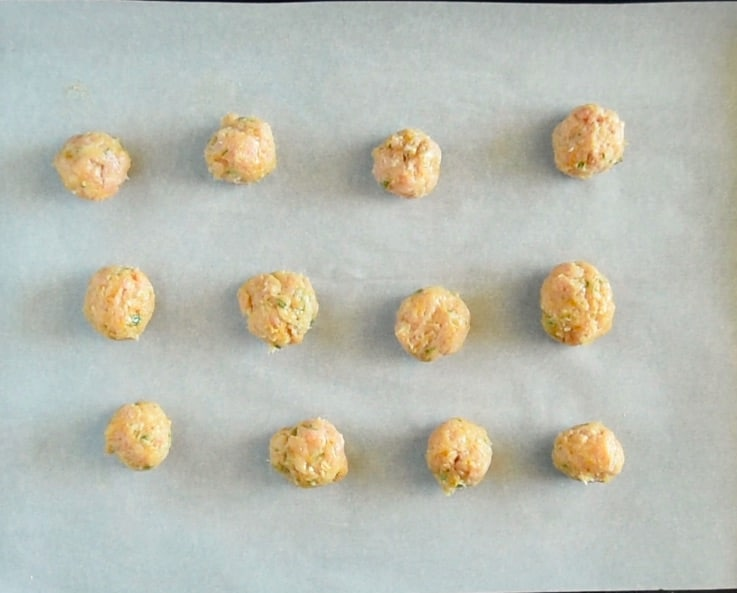 MIni Indian meatballs are lined up on a baking sheet ready to be baked
