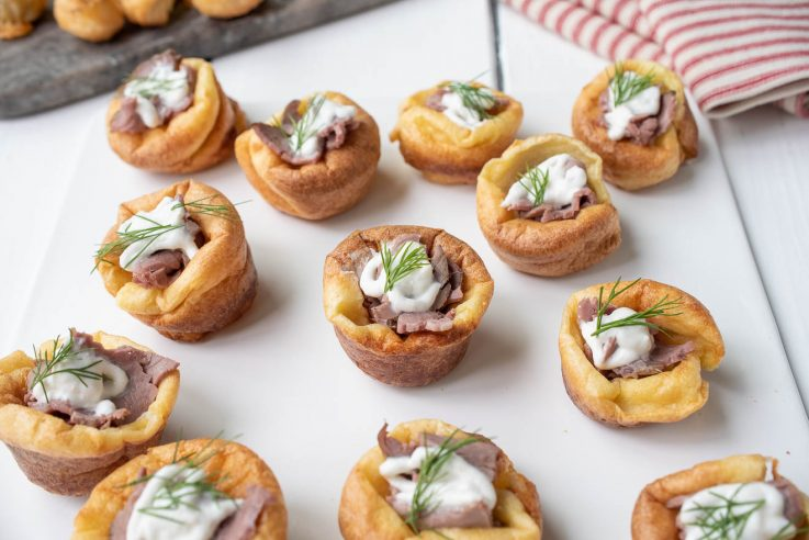 Golden brown mini Yorkshire puddings are filled with sliced roast beef and horseradish sauce