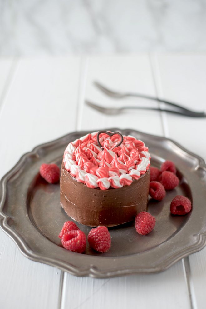 Mini chocolate cake for two on a grey plate with fresh raspberries