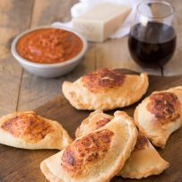 Mini ham and cheese calzones on a board with marinara sauce