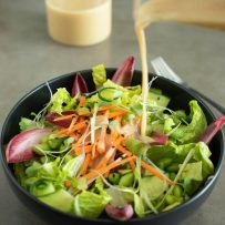 Pouring miso dressing onto a bowl of salad greens and vegetables