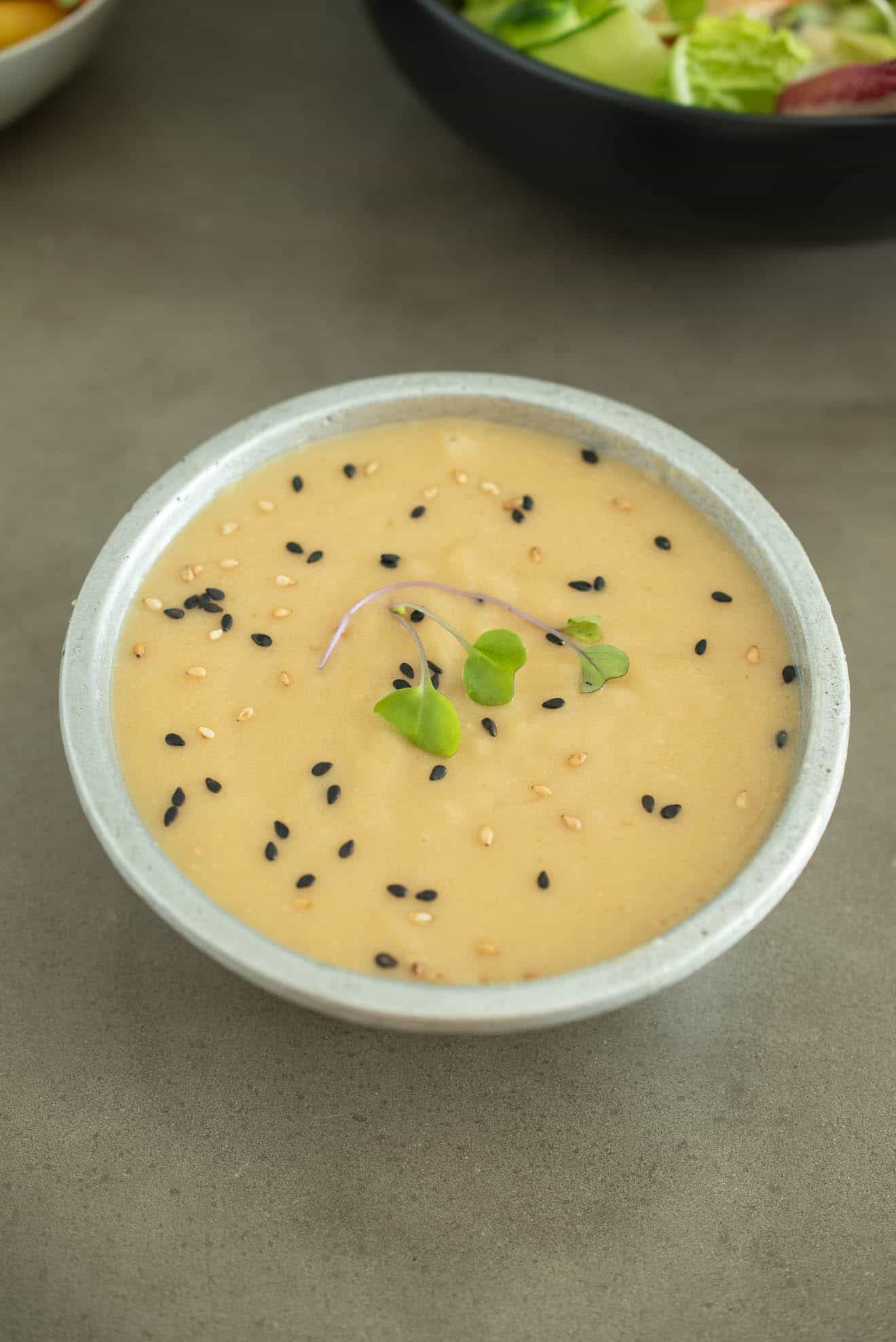 A grey bowl of miso dressing sauce and marinade topped with micro greens and sesame seeds