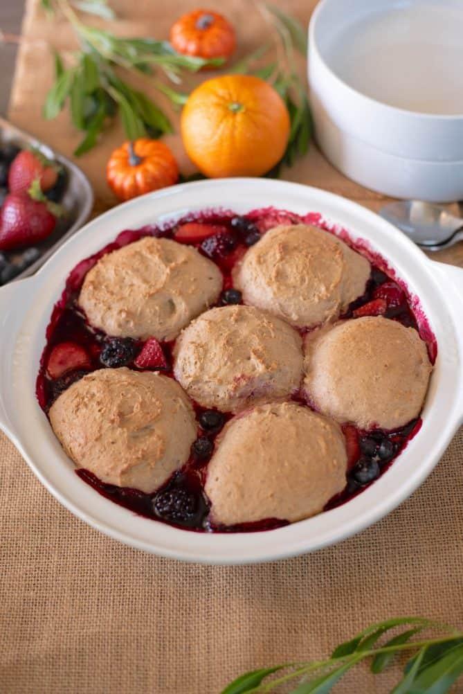 6 pecan dumplings on top of mixed berry cobbler in a white baking pan