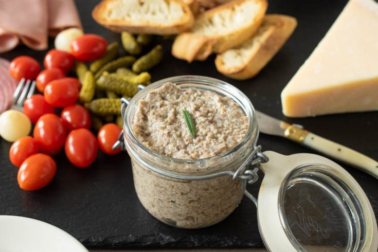 A jar of mushroom pâté on a slate board with cherry tomatoes, cheese and bread