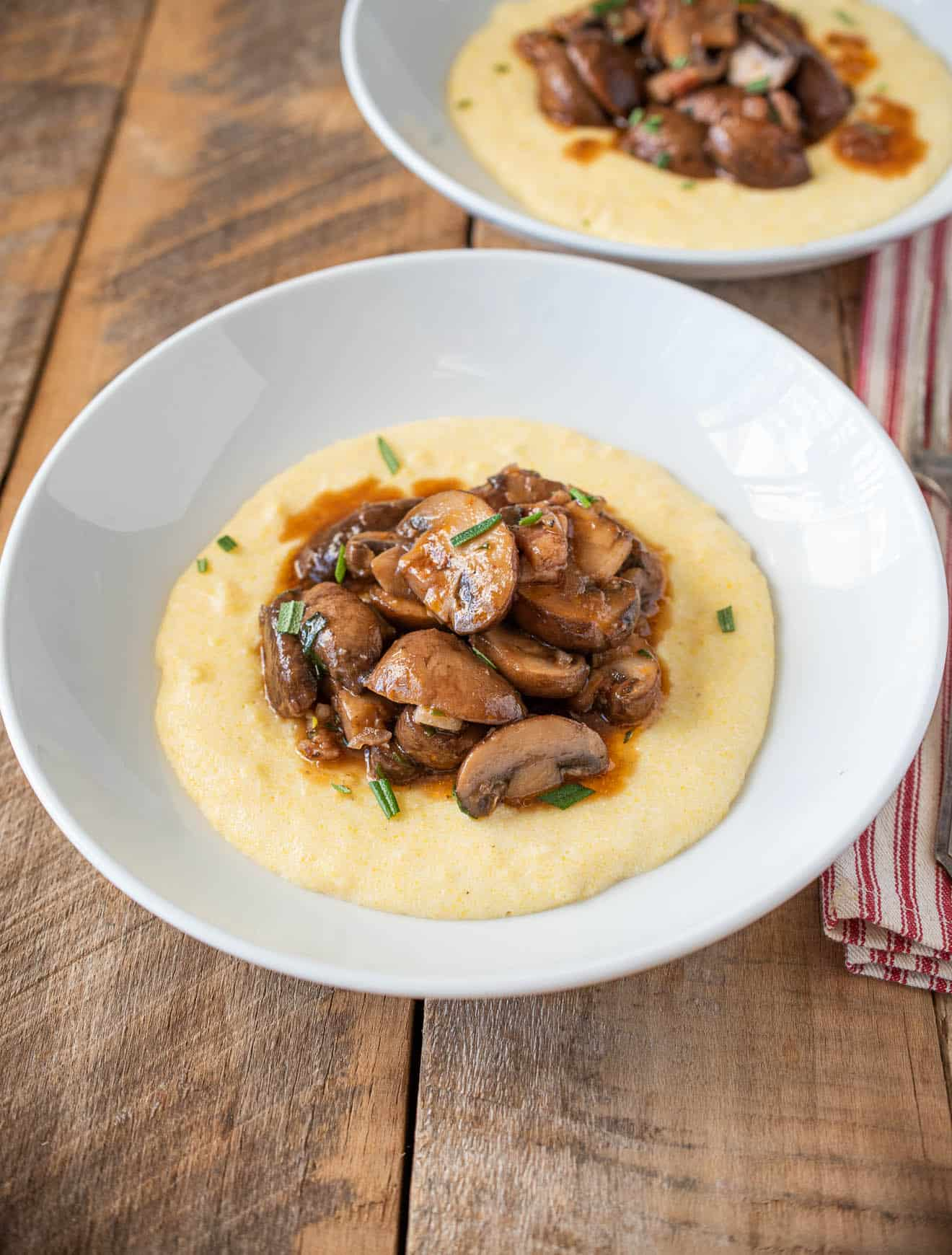 A white bowl of mushroom pancetta ragu served over polenta