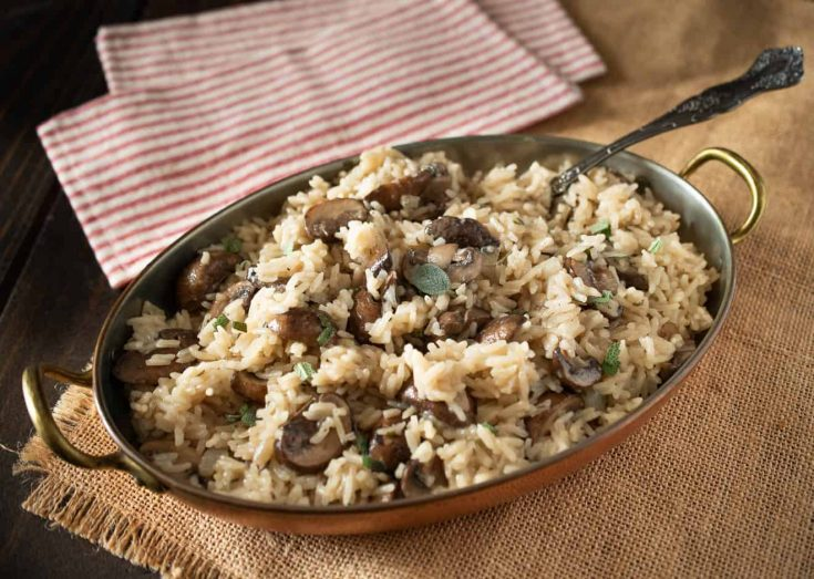 A copper serving dish full of mushroom and sage rice pilaf