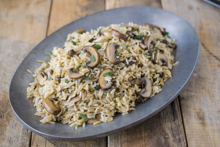 Rice cooked with mushrooms and sage served on an oval pewter dish