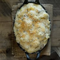 Mushroom sage mac and cheese baked in an oval cast iron skillet