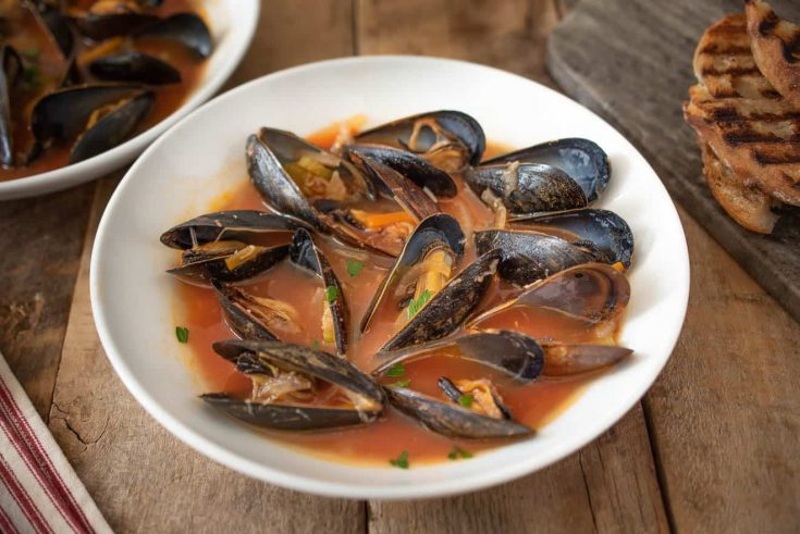 A large bowl of mussels in tomato broth with grilled bread