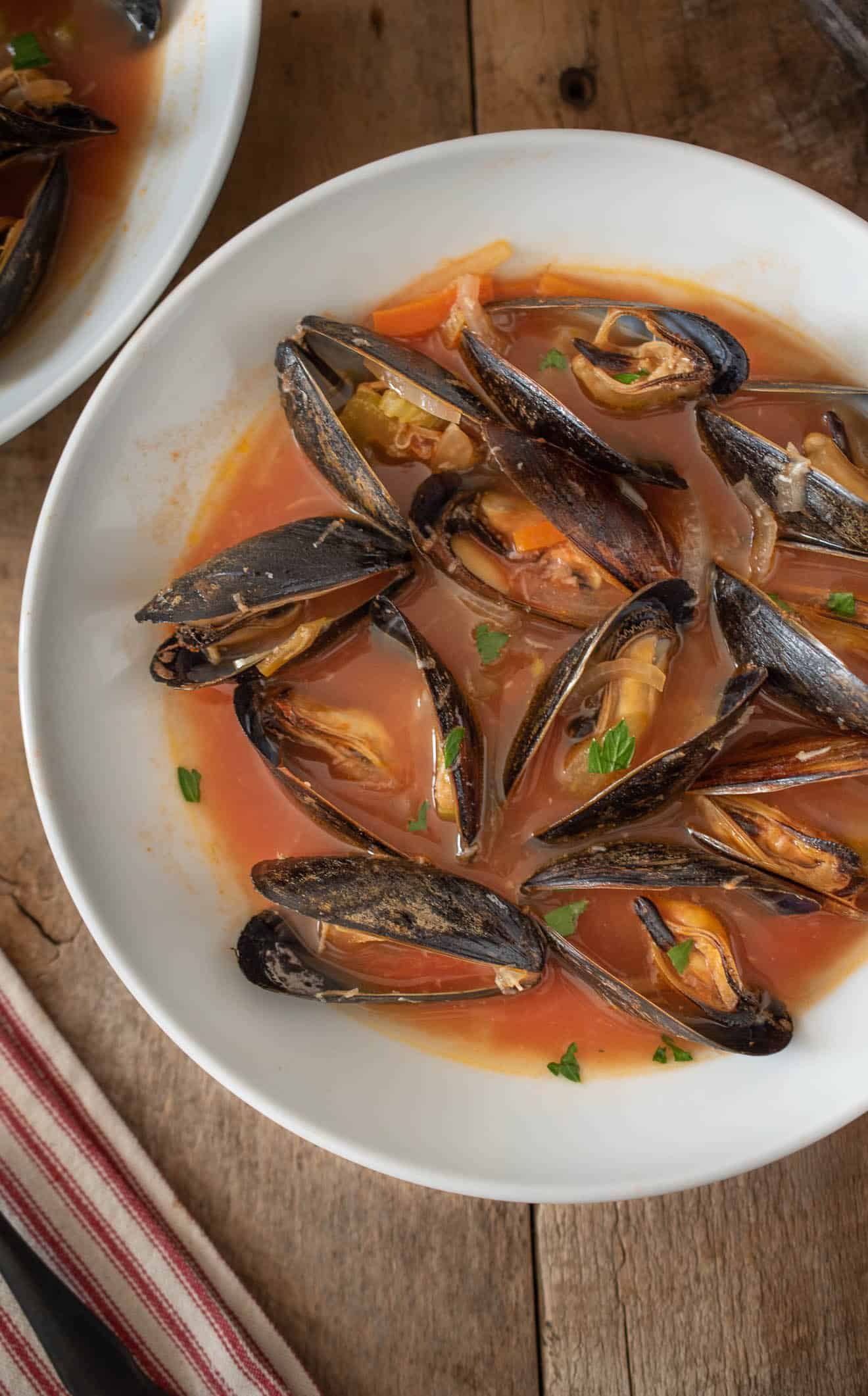 A closeup showing the mussels in their shells garnished with parsley