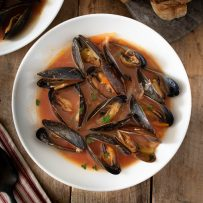 A bowl of mussel soup with crusty bread