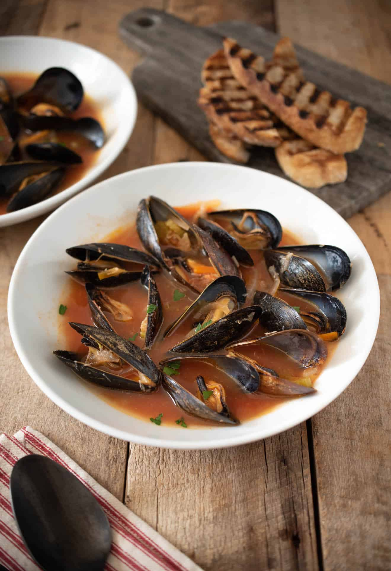Mussel Soup in a white bowl served with grilled bread