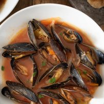 Amazing fresh mussels all opened up in a bowl of tomato based soup