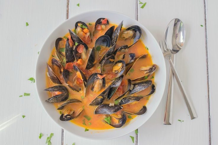 An overhead image of the bowl of mussel soup with 2 spoons