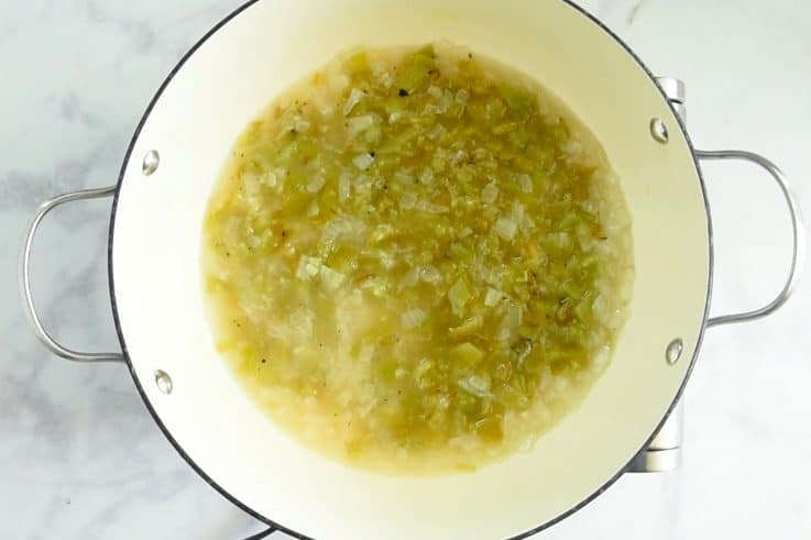 A pan of simmering green chile sauce