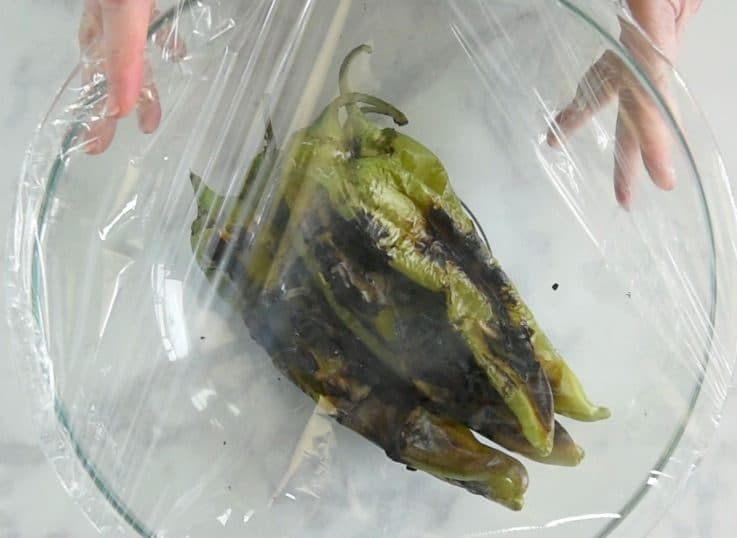 Charred peppers in a glass bowl covered with plastic wrap