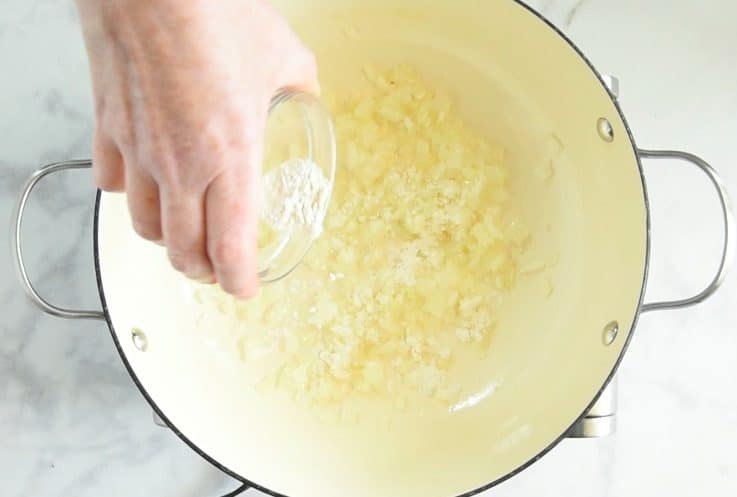 All purpose flour being sprinkled into the pan of onions and garlic