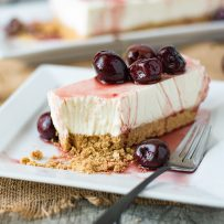 A slice of no bake cherry lemon cheesecake on a white plate with a fork