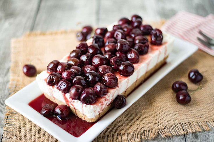 A rectangle shaped no bake cherry cheesecake topped with whole fresh cherries