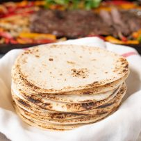 A stack of flour tortillas in a towel to keep them warm