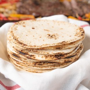 Charred flour tortillas stacked and ready to make tacos