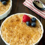 A rice pudding in a white ramekin with a bruleed sugar top with a raspberry and blueberries