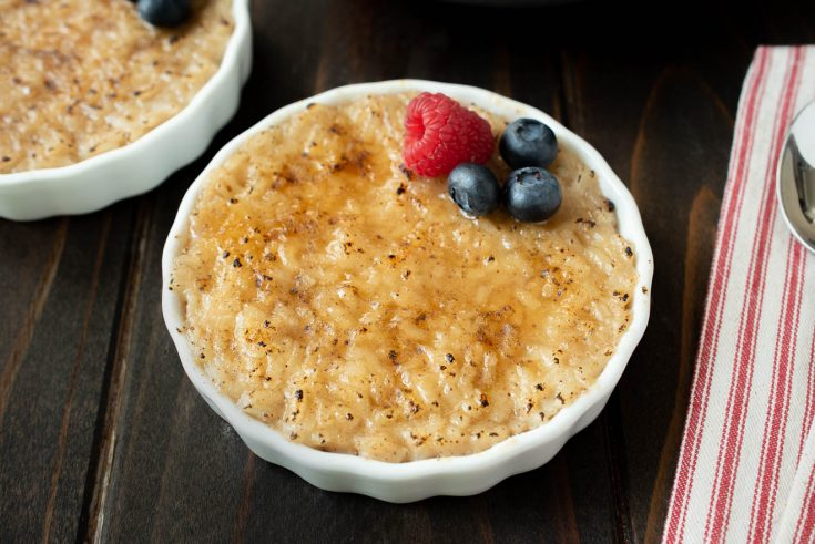A white bowl of rice pudding with a raspberry and blueberries