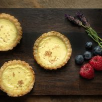 3 small egg custard tarts with raspberries, blueberries and fresh lavender flowers