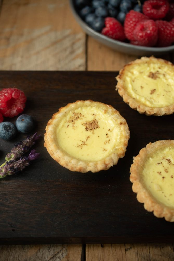 Small egg custard tarts on a presentation board with fresh lavender and berries for garnish