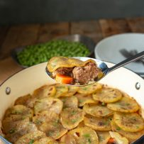 A serving spoon of lamb, carrots and potatoes
