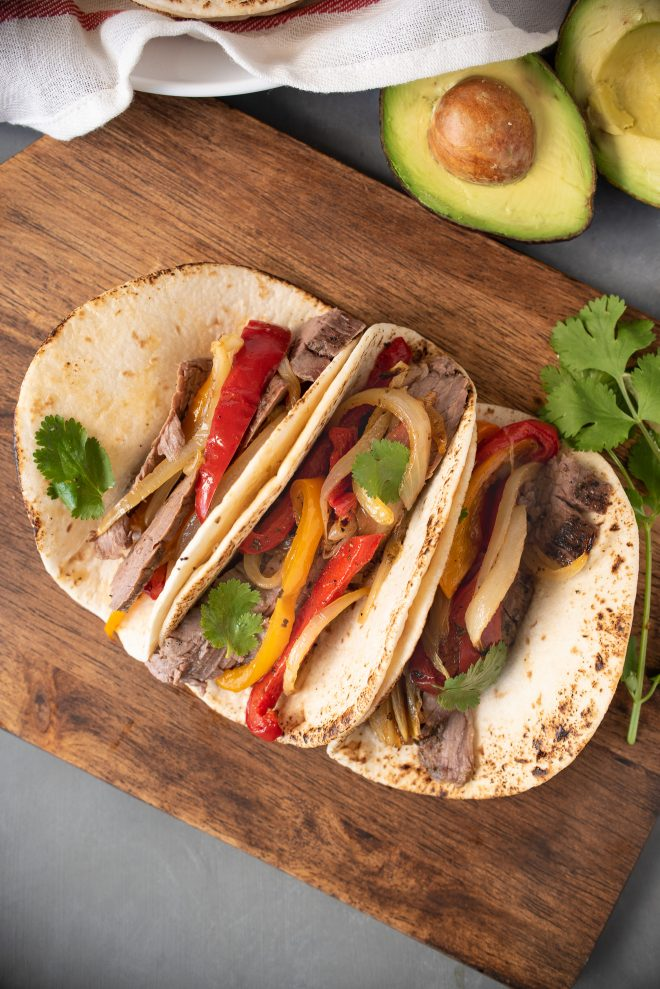 3 flour tortillas filled with steak fajitas. Sliced beef, onions and peppers
