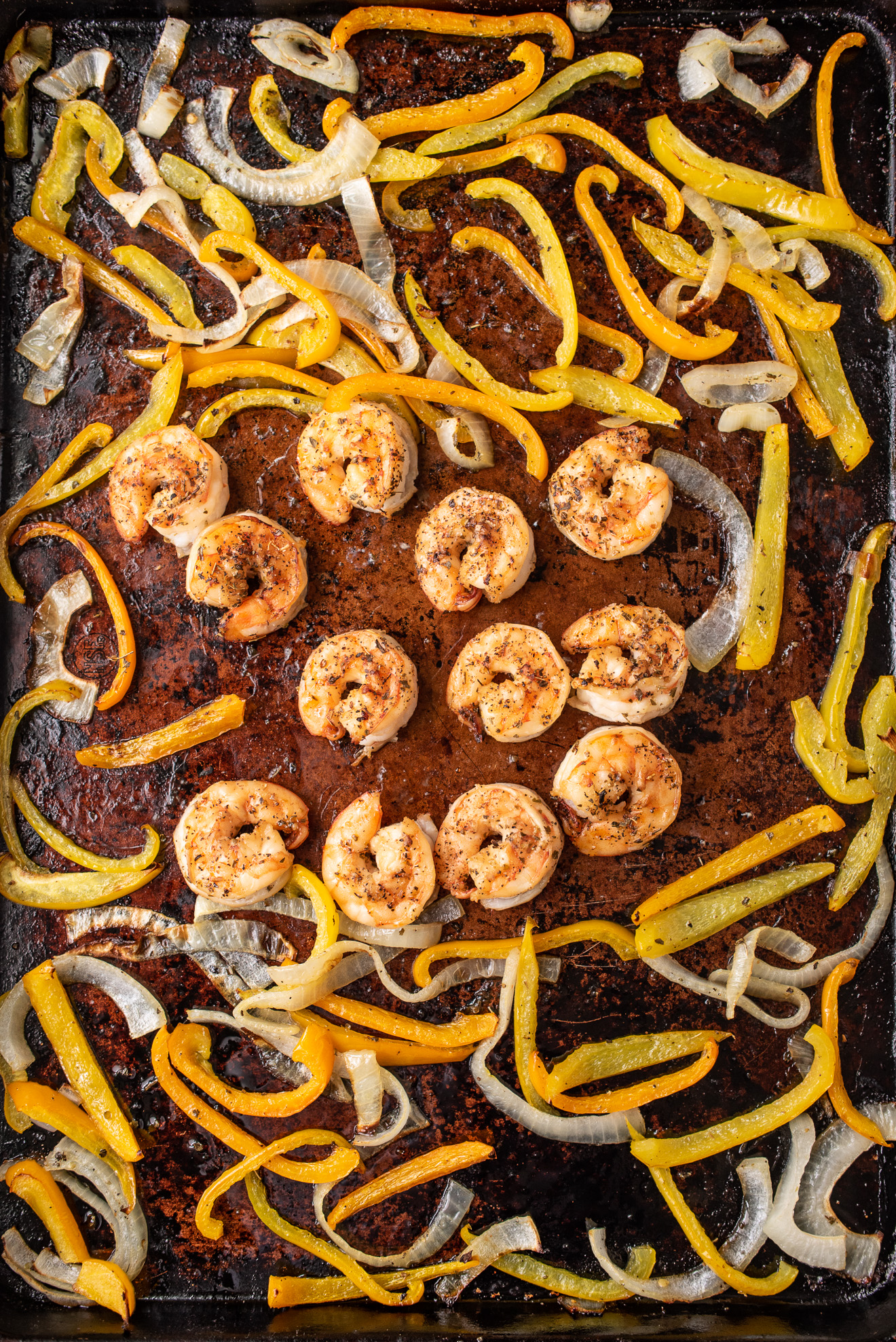 Shrimp, peppers and onions on a sheet tray