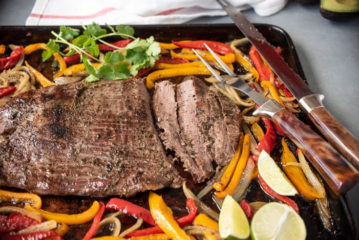 Sliced beef on a sheet pan with onions and peppers