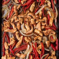 A large baking sheet of roasted chicken fajitas with red peppers and onion