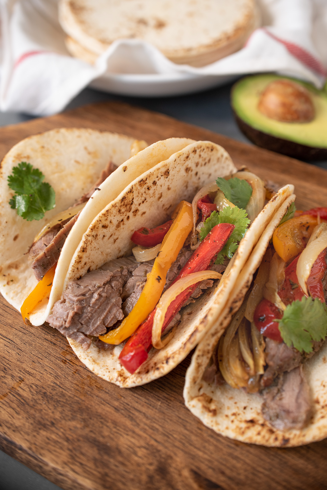 Sliced beef, onions and peppers in tortillas