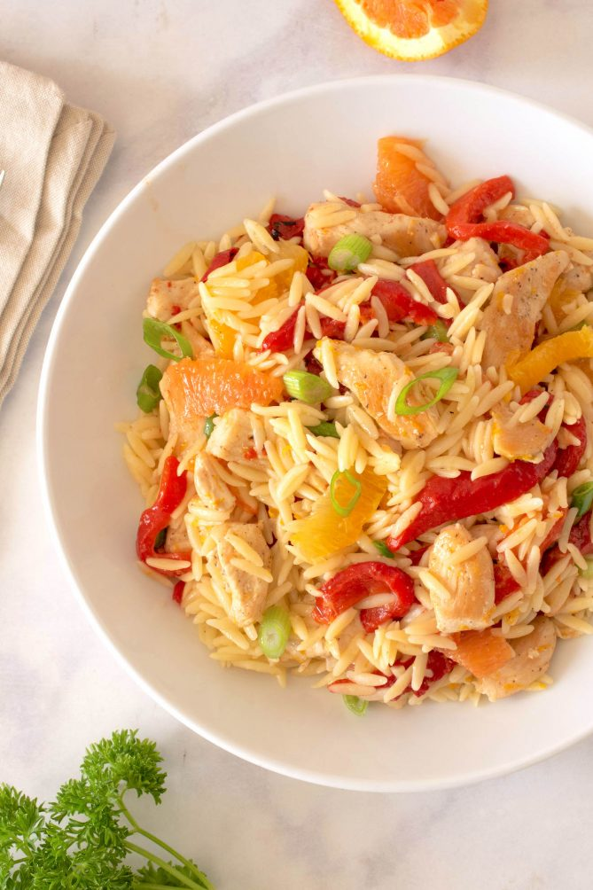 A closeup showing the red peppers, orange segments, chicken and green onions