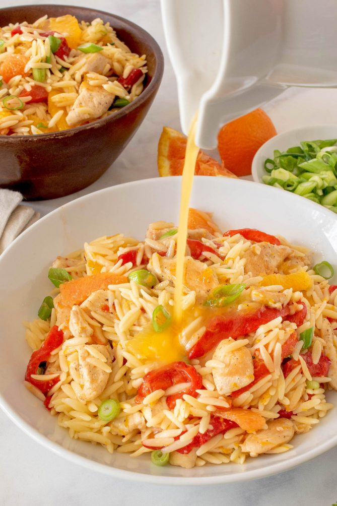 Orzo chicken salad being dressed with orange dressing