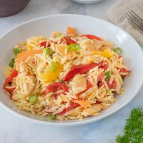 Colorful orange segments, roasted red peppers in an orange chicken orzo salad