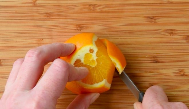 Cutting the peel off an orange
