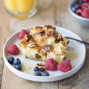 A slice of the French toast casserole on a white plate with blueberries and raspberries