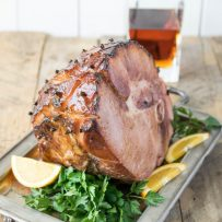 A beautifully glazed ham on a serving tray garnished with orange sliced and parsely