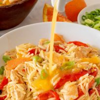 Pouring orange dressing over chicken orzo salad