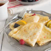 Folden pancakes on a plate with raspberries and blackberries