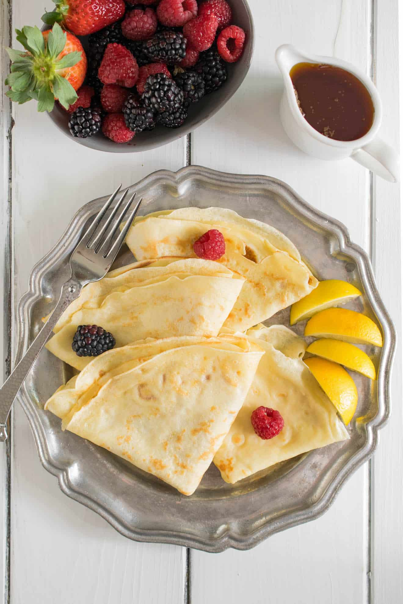 Thin crepe pancakes with lemon wedges fruit and syrup from overhead
