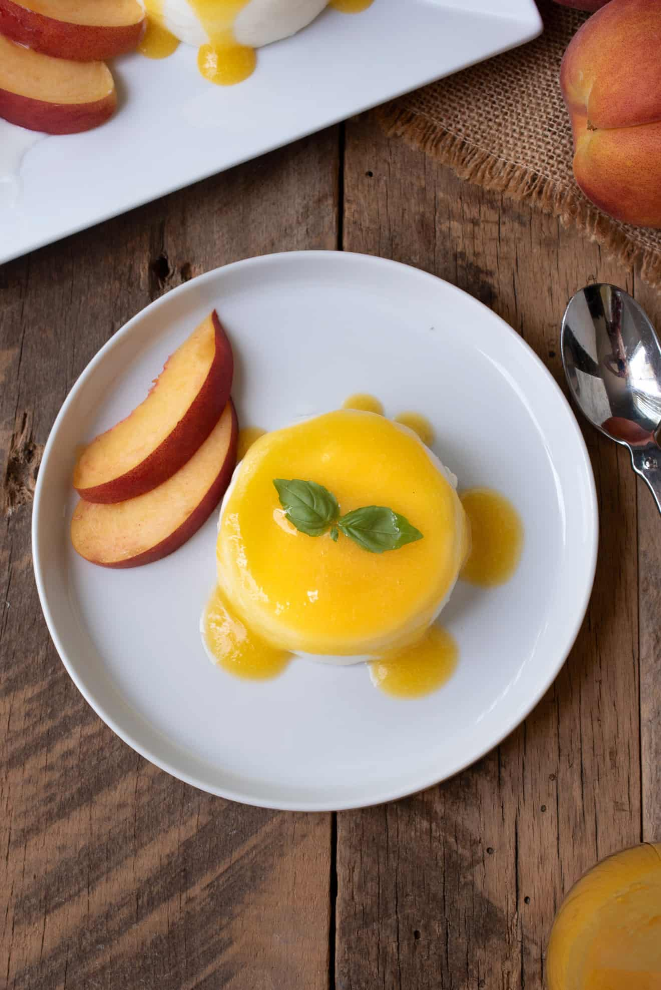 Panna cotta with peach sauce, peach slices and basil leaves