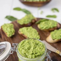 Pea and mint pesto in a jar with some on crostini in background