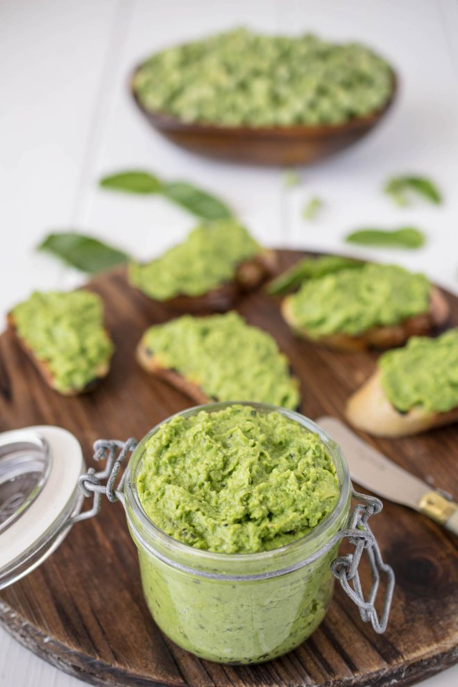 Pea & mint pesto in a jar with some on crostini in background
