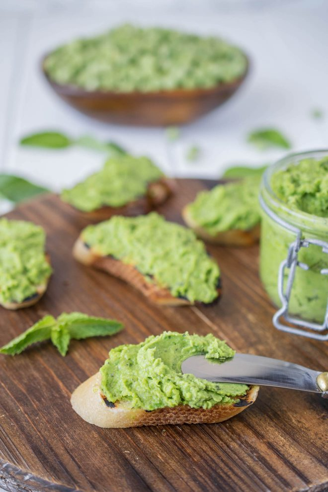 Using a knife to spread the pesto on a crusty piece of bread