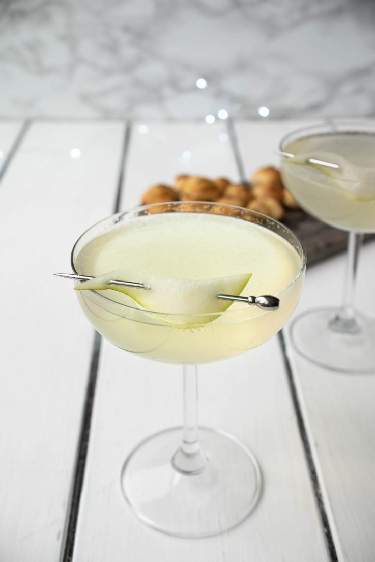 Pear Ginger Champagne Cocktail in a stemmed glass garnished with a pear slice